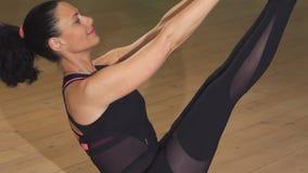 Sluit omhoog van een mooie vrouw die yoga in evenwicht brengende oefening doen stock video