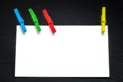 Sluit omhoog van een notadocument en wasknijpers Stock Fotografie