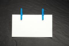 Sluit omhoog van een notadocument en wasknijpers Stock Foto