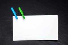 Sluit omhoog van een notadocument en wasknijpers Stock Afbeeldingen
