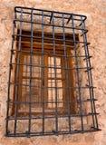 sluit omhoog van een oud houten venster met bars van ijzer die de toegang, in een muur van concreet en steen in een verlaten huis stock afbeelding