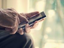 Sluit omhoog van een oude mens is gelukkig met het typen van mobiele slimme telefoon Stock Afbeelding