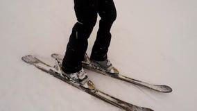 Sluit omhoog van een persoon die onderaan een berghelling ski?en stock video