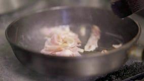 Sluit omhoog van een plak van bacon in een gietijzerpan die in brand wordt gestoken stock video