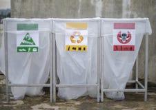 Sluit omhoog van een reeks van het recycling van bakken met kleur gecodeerde secties voor algemeen afval stock foto