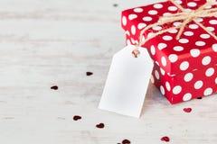Sluit omhoog van een rode gestippelde giftdoos over witte houten achtergrond De ruimte van het exemplaar Lege Nota Stock Foto