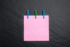 Sluit omhoog van een roze notadocument en wasknijpers Royalty-vrije Stock Foto