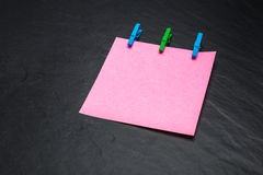 Sluit omhoog van een roze notadocument en wasknijpers Stock Afbeelding