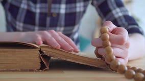 Sluit omhoog van een rozentuin in de handen van een vrouw die de Bijbel lezen stock video