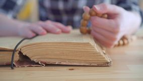 Sluit omhoog van een rozentuin in de handen van een vrouw en de open Bijbel stock footage