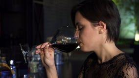 Sluit omhoog van een schitterend brunette genietend van drinkend wijn bij de bar glimlachend aan de camera stock footage