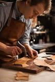 Sluit omhoog van een schoenmakersmens die met leer werken stock fotografie