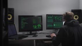 Sluit omhoog van een spion met smartwatch en mobiele telefoonzitting bij de lijst met computermonitors Hakker die proberen te ber stock videobeelden