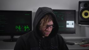 Sluit omhoog van een spion met smartwatch zitting en het gebruiken van laptop met computermonitors achter hem Misdadige mens in o stock video