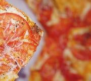 Sluit omhoog van een stuk van pizza op een pizzaachtergrond stock foto's