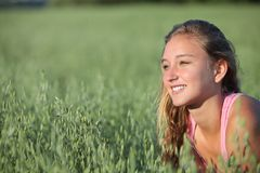 Sluit omhoog van een tienermeisje die in een haverweide glimlachen royalty-vrije stock foto's