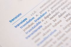 Sluit omhoog van een TRANSLATE woord in een woordenboek stock foto