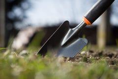 Sluit omhoog van een tuinschop die aan grond wordt neergestoken; spring het werk op Stock Foto