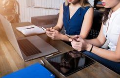 Sluit omhoog van een twee hipstermeisjes die online praatje op mobiele telefoons na het werk aangaande laptop computer hebben stock foto