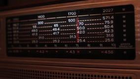 Sluit omhoog van een uitstekende radiowijzerplaat die met de posten en de frequenties worden gestemd stock video