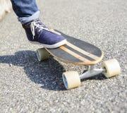 Sluit omhoog van een vleet en tennisschoenschoenen op het asfalt Stock Afbeeldingen