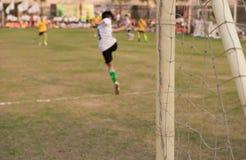 Sluit omhoog van een voetbaldoel met jonge geitjes het spelen Royalty-vrije Stock Fotografie