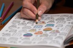 Sluit omhoog van een vrouw die een tekening van de spanningsversie kleuren Stock Foto's