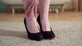 Sluit omhoog van een vrouw die in hielen haar benen na het werk masseren stock footage