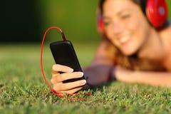 Sluit omhoog van een vrouw die met hoofdtelefoons een slimme telefoon houden Royalty-vrije Stock Foto