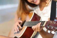 Sluit omhoog van een vrouw het spelen gitaar op het strand Stock Afbeeldingen
