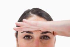 Sluit omhoog van een vrouw met haar hand op haar voorhoofd stock afbeelding