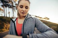 Sluit omhoog van een vrouwelijke atleet die tijd controleren terwijl het lopen op weg Geschiktheidsvrouw die haar polshorloge tij royalty-vrije stock foto's