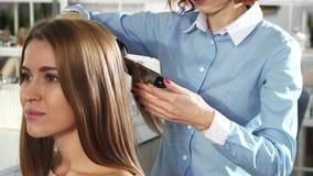 Sluit omhoog van een vrouwelijke hairstlist gebruikend het krullen ijzerbewerking met haar vrouwelijke cliënt royalty-vrije stock foto's