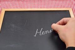 Sluit omhoog van een vrouwelijke hand schrijvend op een bord het menu voor t Stock Afbeelding