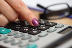 Sluit omhoog van een vrouwelijke vrouw die op calculatorknoop drukken met ey Stock Foto