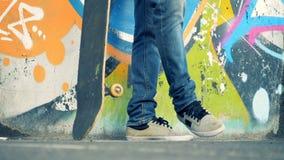 Sluit omhoog van een vuil skateboard worden die die door een man been wordt opgeheven stock video