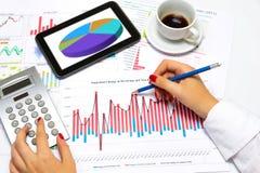 Sluit omhoog van een wijfje overhandigt, doend bedrijfsstatistieken, bij bureau Stock Afbeeldingen
