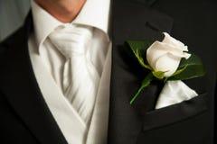 Sluit omhoog van een wit roze corsage op een Bruidegom Stock Fotografie