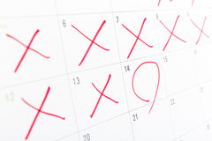 Sluit omhoog van een witte die kalenderpagina met wat de dagen van rood X worden gekruist royalty-vrije stock foto's