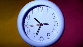 Sluit omhoog van een witte klok op kleurrijke achtergrond stock videobeelden