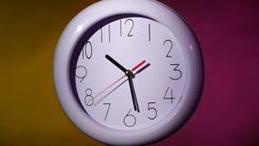 Sluit omhoog van een witte klok op kleurrijke achtergrond stock video