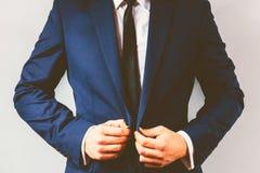 Sluit omhoog van een zakenman die zijn kostuum dichtknopen Stock Afbeeldingen