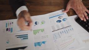 Sluit omhoog van een zakenman overhandigt met pen die bij bureau werken en grafieken en grafieken analyseren en zaken schrijven stock footage