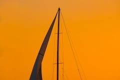 Sluit omhoog van een zeilsilhouet onder een oranje hemel bij zonsondergang stock fotografie