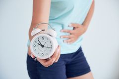 Sluit omhoog van een zieke jonge vrouw met een klok in haar handen het concept regelgeving van de menstruele cyclus tijd om h te  Royalty-vrije Stock Foto's