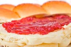 Sluit omhoog van een zoet broodje met aardbeijam Stock Afbeelding