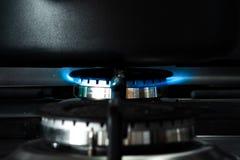 Sluit omhoog van een zwarte pan die bovenop een open vlam van een gashaardplaat omhoog verwarmend wordt gezeten de inhoud binnen  stock afbeeldingen