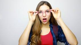 Sluit omhoog van emotioneel ongelovig open mondmeisje met glazen wantrouw concept stock fotografie