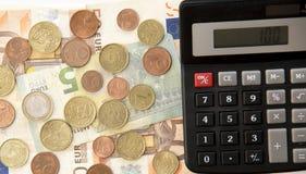 Sluit omhoog van euro munt muntstukken, bankbiljetten en calculator Stock Afbeeldingen
