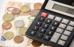 Sluit omhoog van euro munt muntstukken, bankbiljetten en calculator Stock Afbeelding